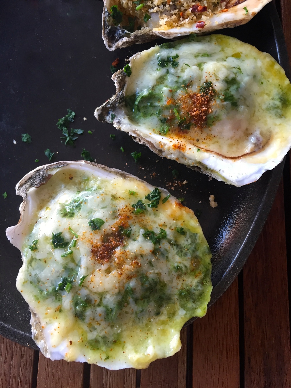 Grilled Oysters Rockefeller withpastis, spinach, lemon zest, aged white cheddar, and cream.