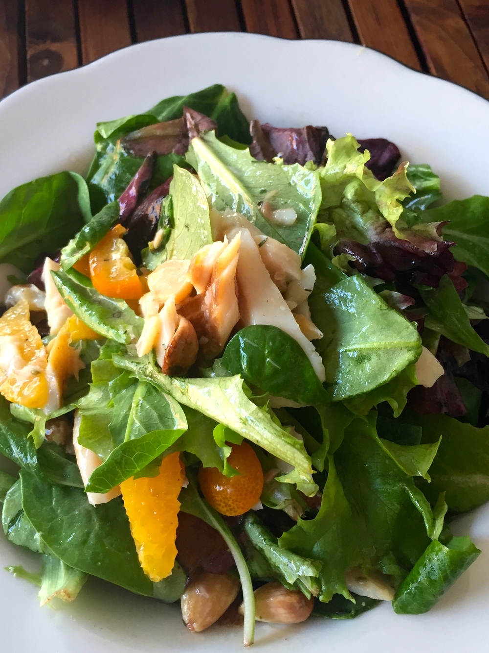 Smoked Trout Salad within-houseapplewood smoked rainbow trout, market lettuce,kumquat, citrus, almonds, dill, and champagne vinaigrette.
