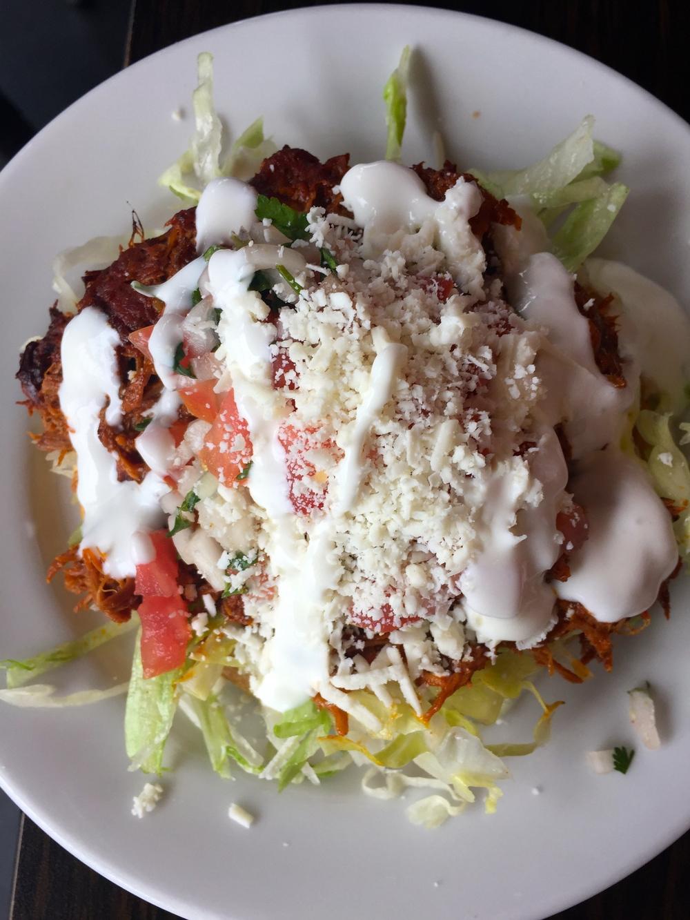 Yucatan-spiced shredded pork Cochinita Pibil Sope, with lettuce, crema, and queso fresco.