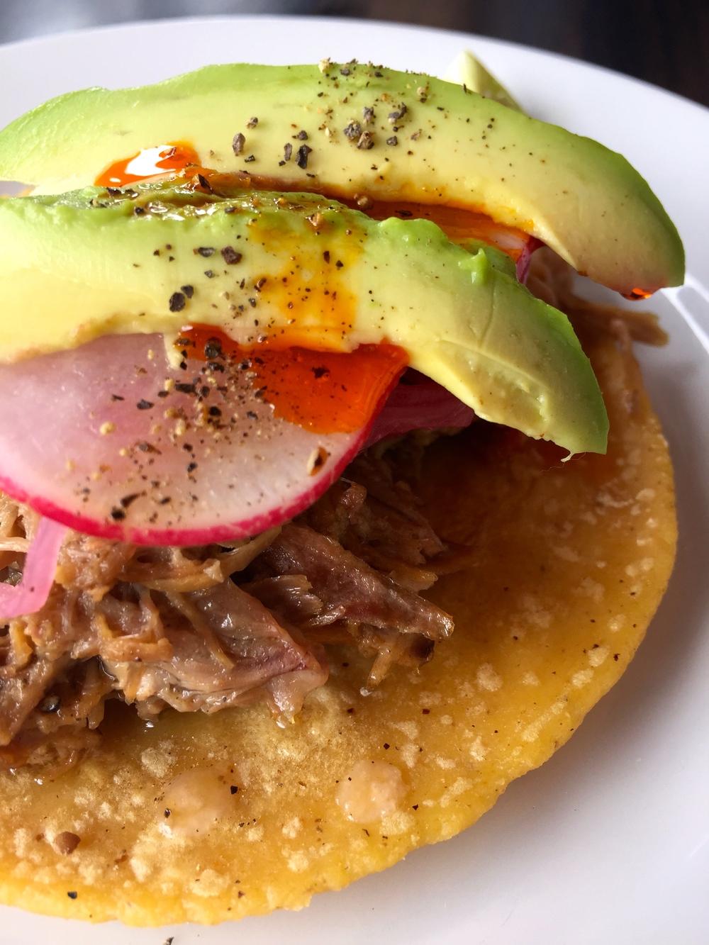 Carnitas de Pato taco with duck confit, avocado, vinegar onion, radishes, and chile oil.