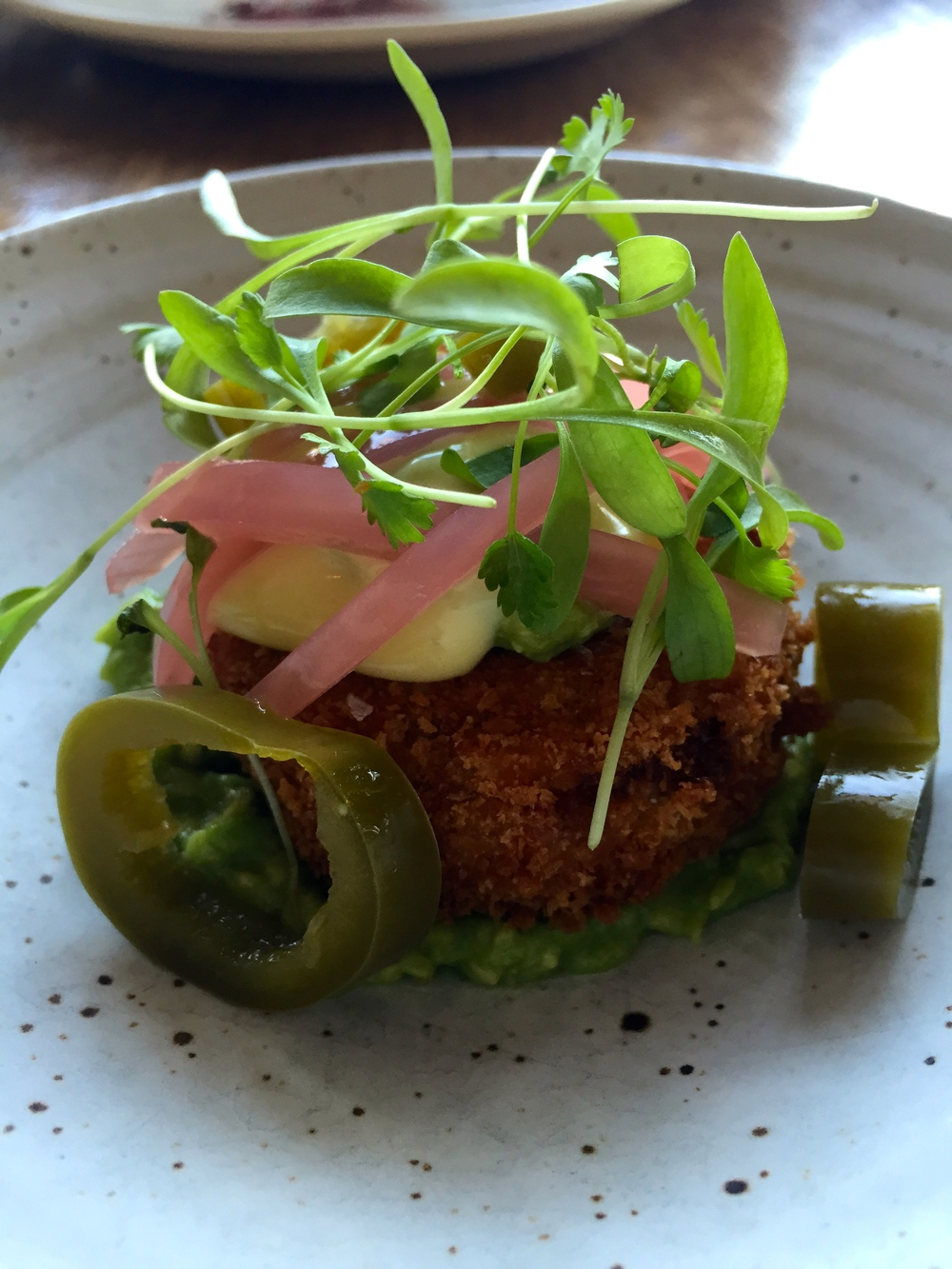"Fried cook pigs pork trotter ""milanesa"" avocado, pickled onion & jalapeno, cilantro, and aioli."