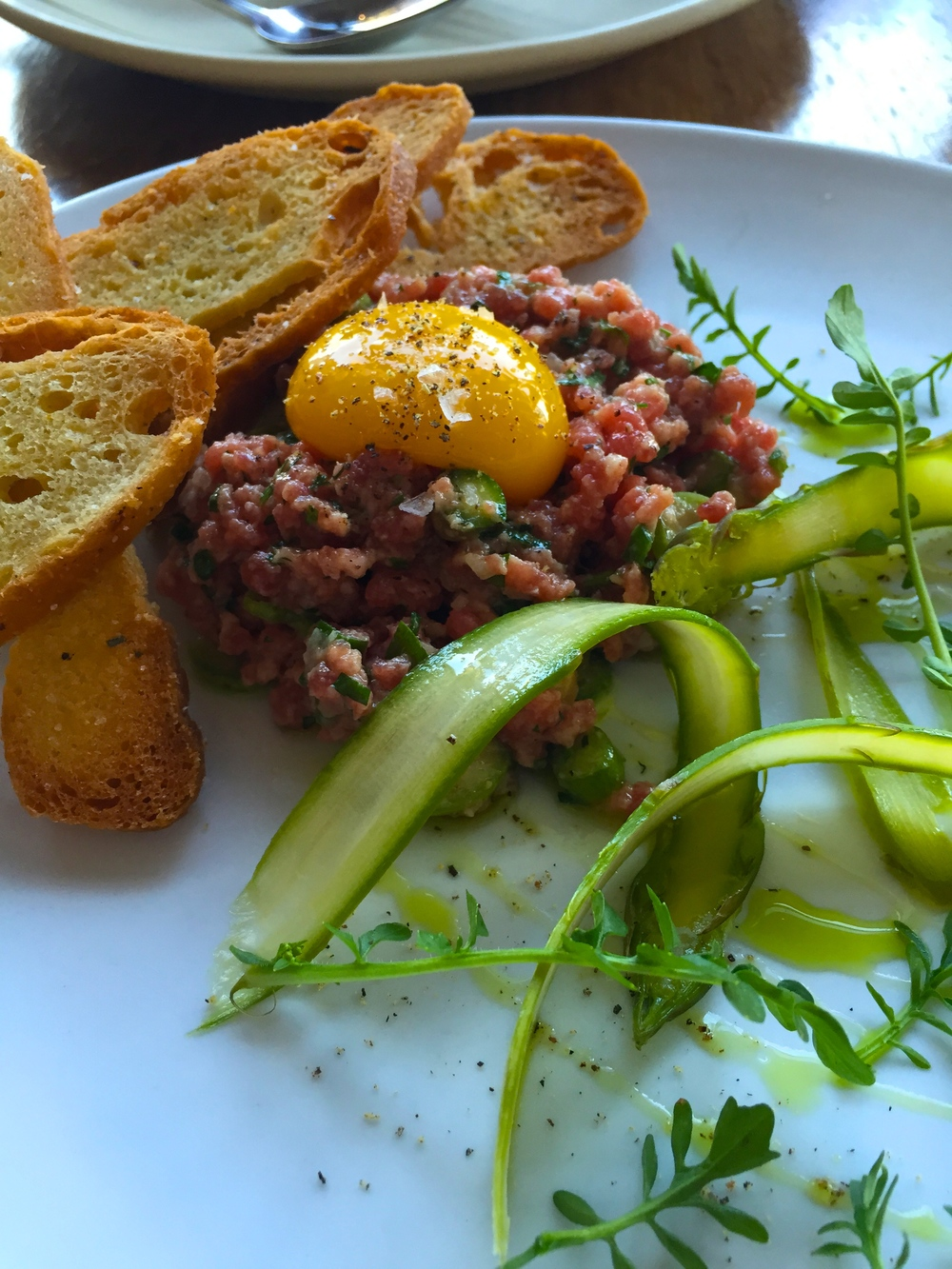Prime Beef & Asparagus Tartare with white soy and yuzu dressing, egg yolk, garlic, chive, and jaime farms watercress.