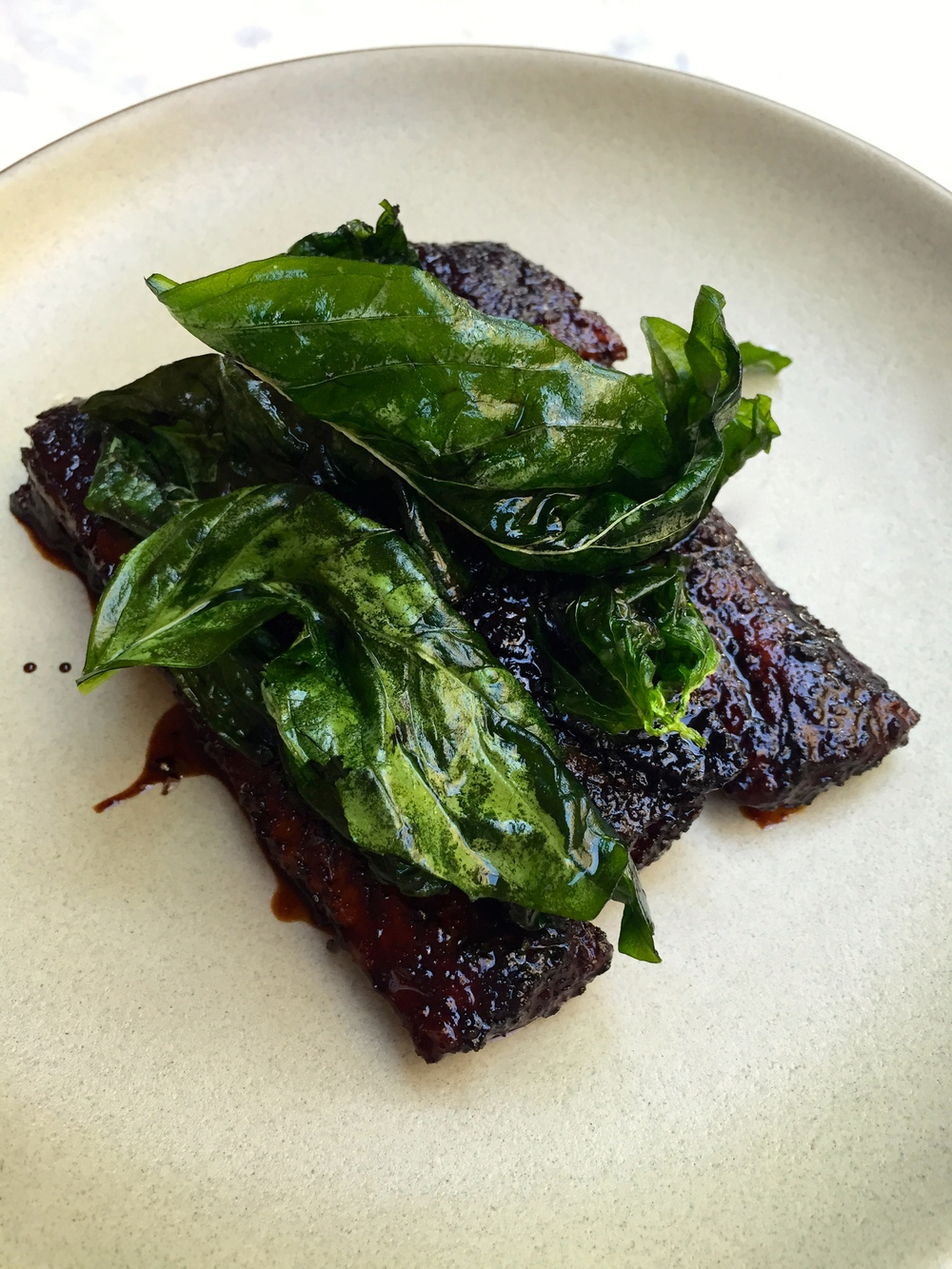 Balsamic glazed ribs with aleppo pepper and fried basil.