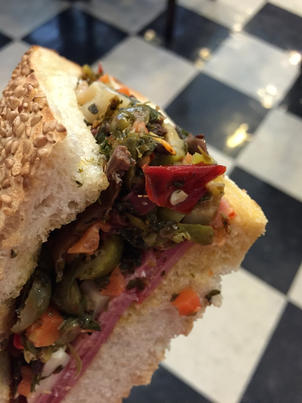 Muffuletta - New Orleans Sicilian sandwich consisting of Genoa Salami, Soppressata, Hot Capicola, and Mortadella meats, Provolone and Mozzarella cheeses, and House-Made Olive Salad on a sesame seeded Leidenheimer loaf.