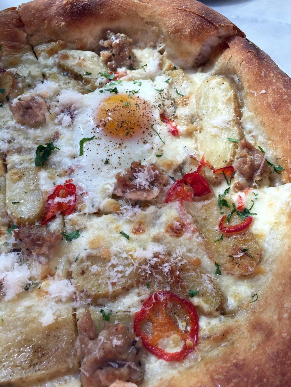 BREAKFAST PIZZA - house sausage, potatoes, pickled chile, rosemary cream, and a farm egg.
