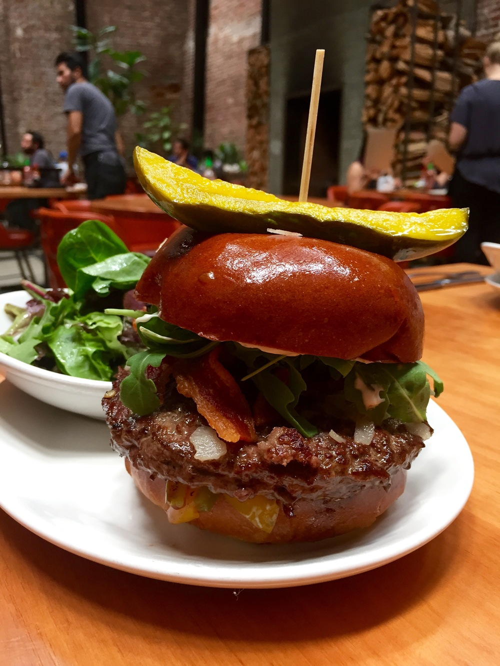 Mohawk Burger with  arugula, parmesan, crispy bacon, red onion, roasted peppers, and rosemary aioli.