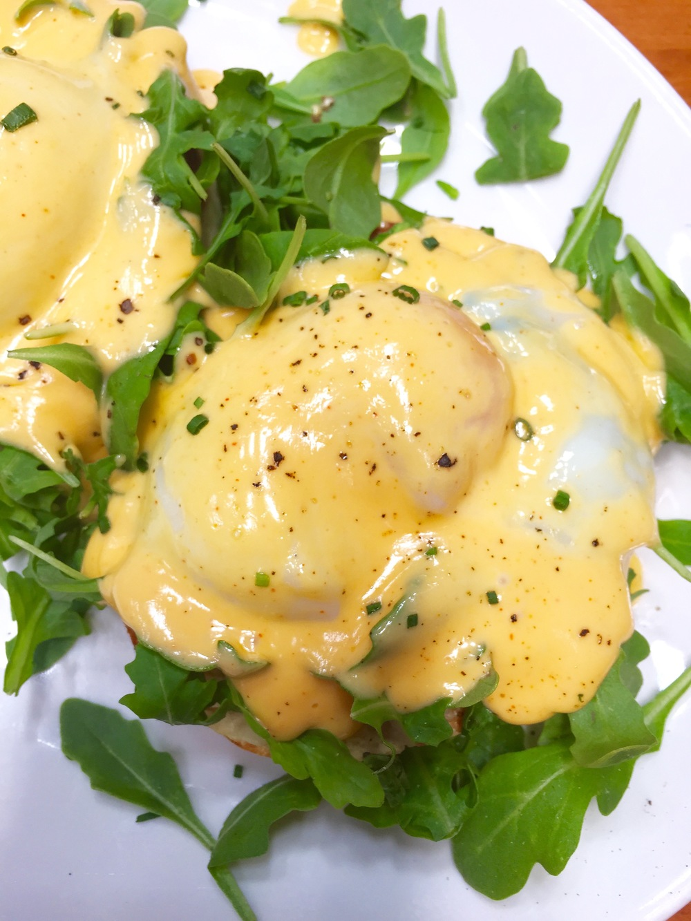 Eggs Benedict with  Canadian bacon, arugula, slow poached eggs, hollandaise, and English muffin.
