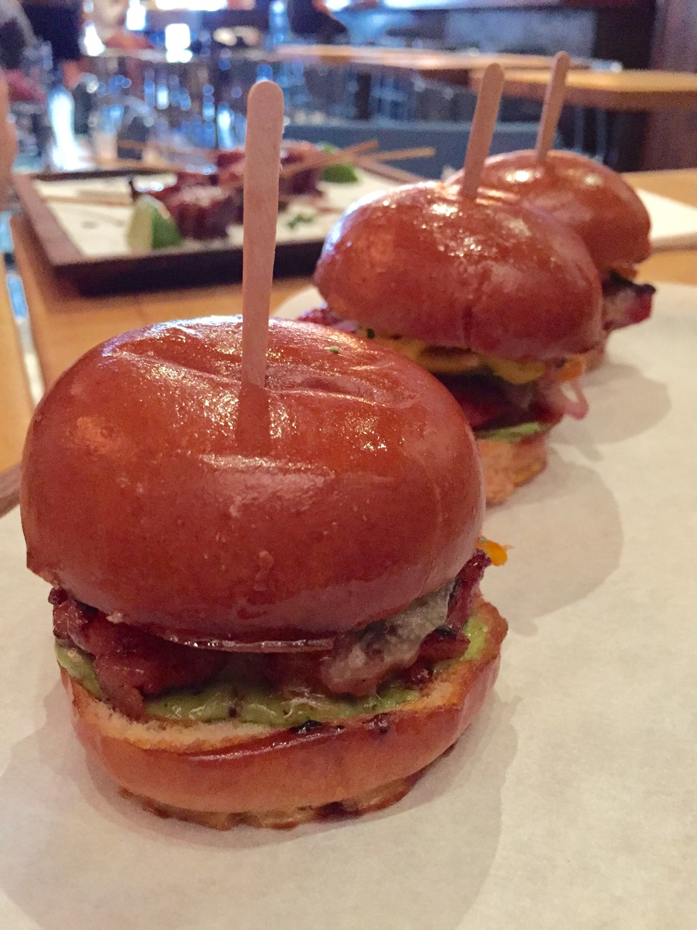 Chorizo Sliders with pickled sweet and spicy peppers, avocado emulsion, and white cheddar.