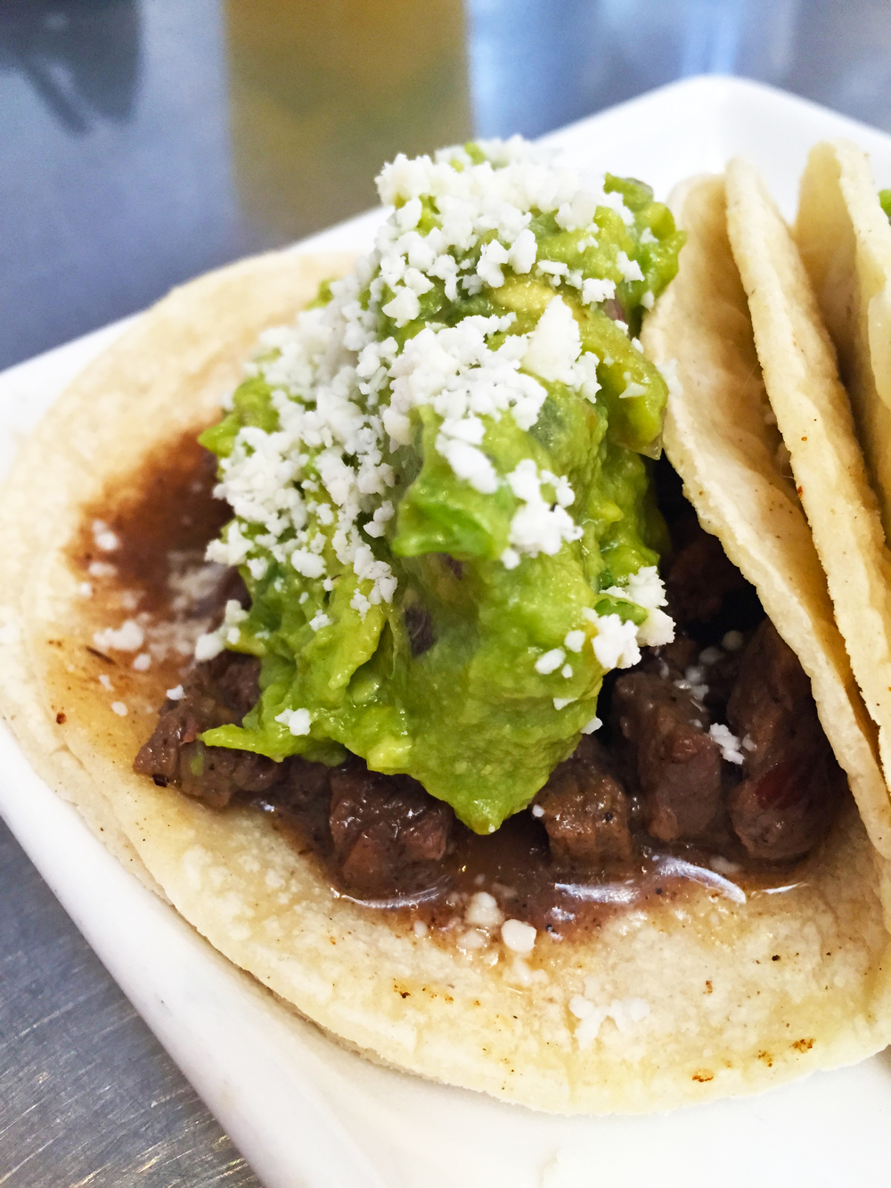 Signature Taco with marinated top sirloin steak, guacamole, and cotija cheese.