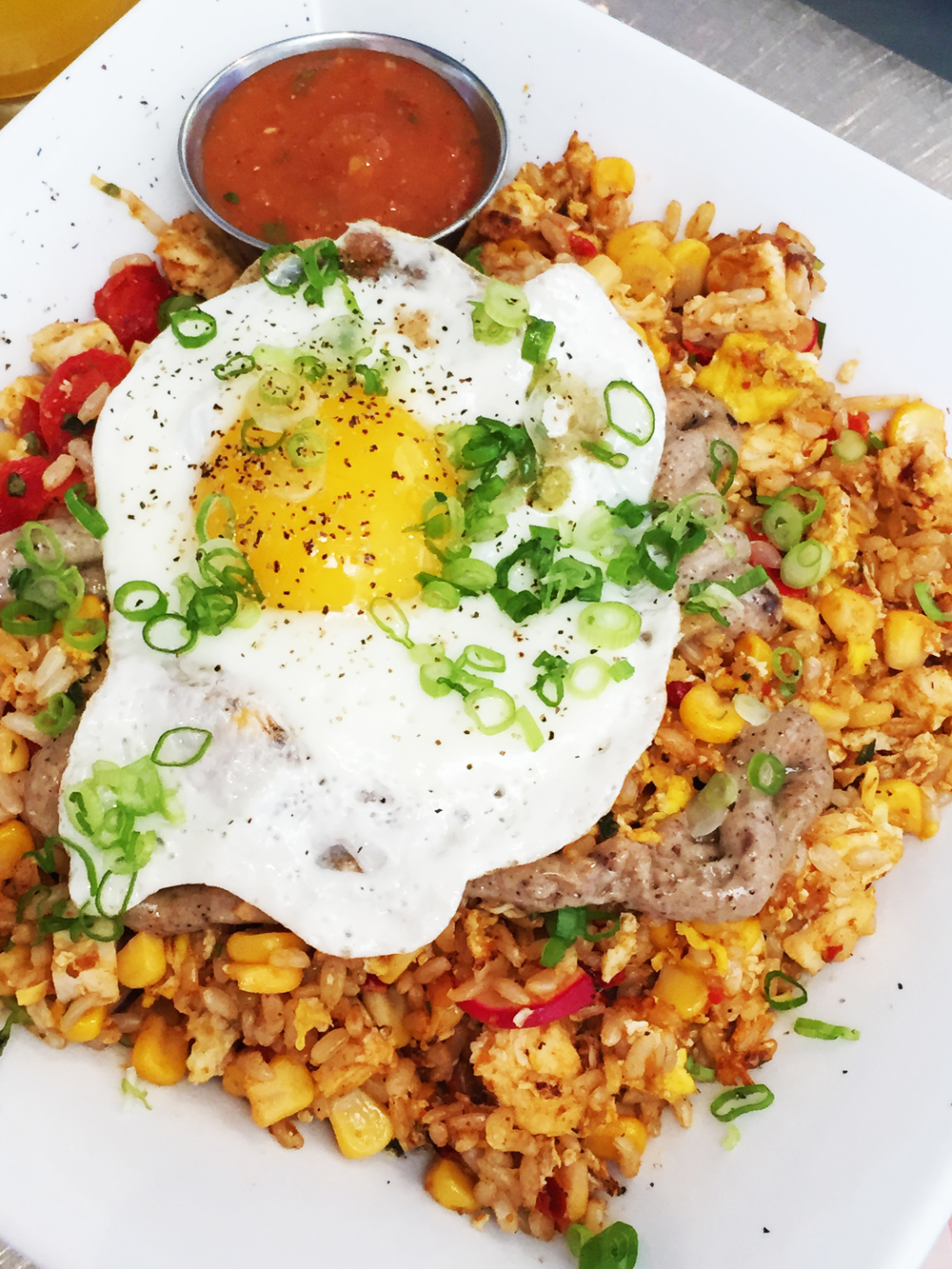 Nasi Goreng - Indonesian fried rice with garlic aioli and corn salad topped off with green onions and a sunny side egg (and optional chicken).