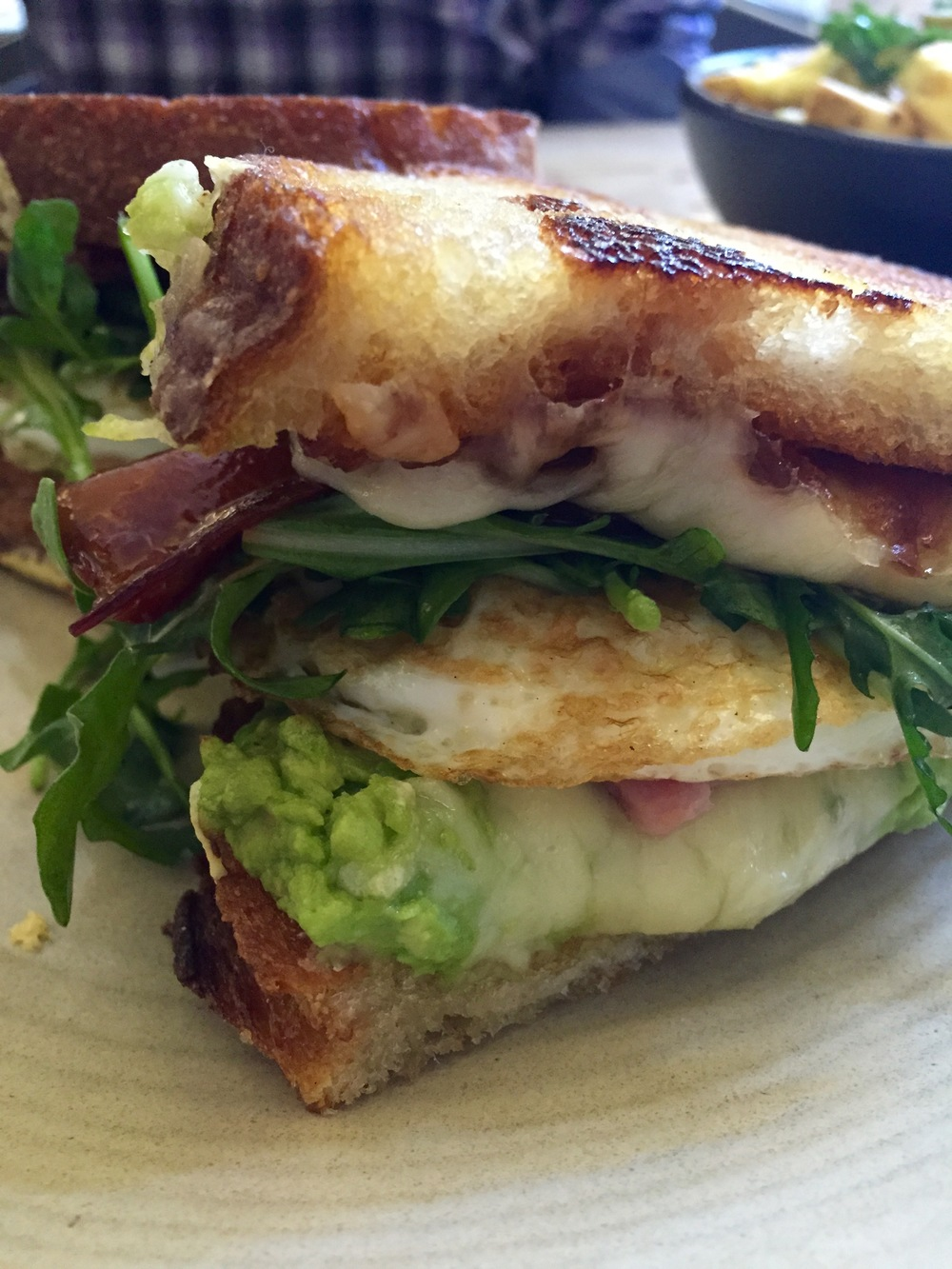 Littlefork Melt with Maple Bacon, ham, onion marmalade, avocado, eggs over-easy, cheddar, and Jarlsberg.