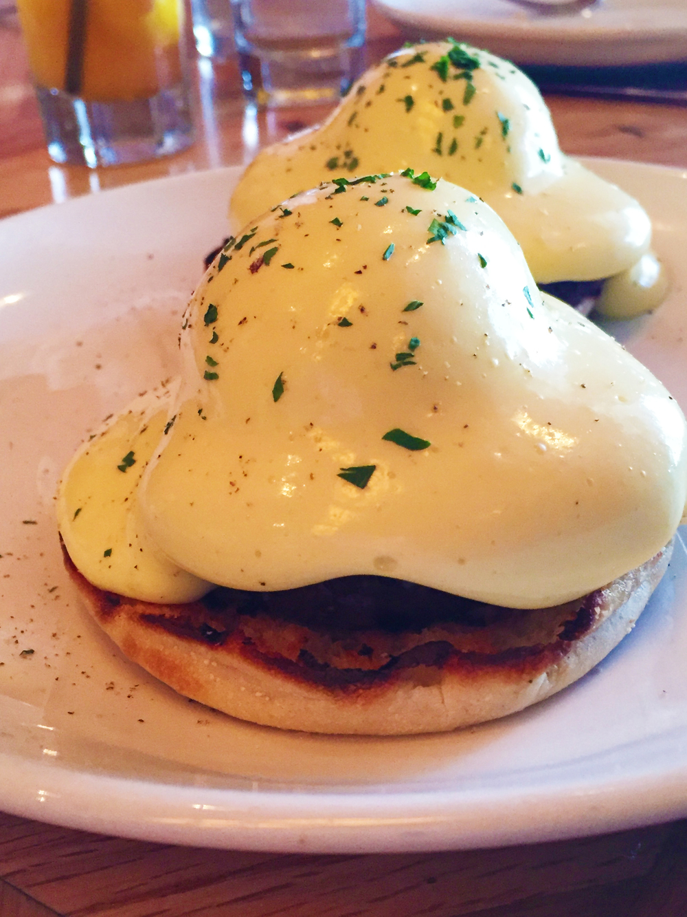 Smoked Pork Benedict with smoked pork roast, tomato, hollandaise, and english muffin.