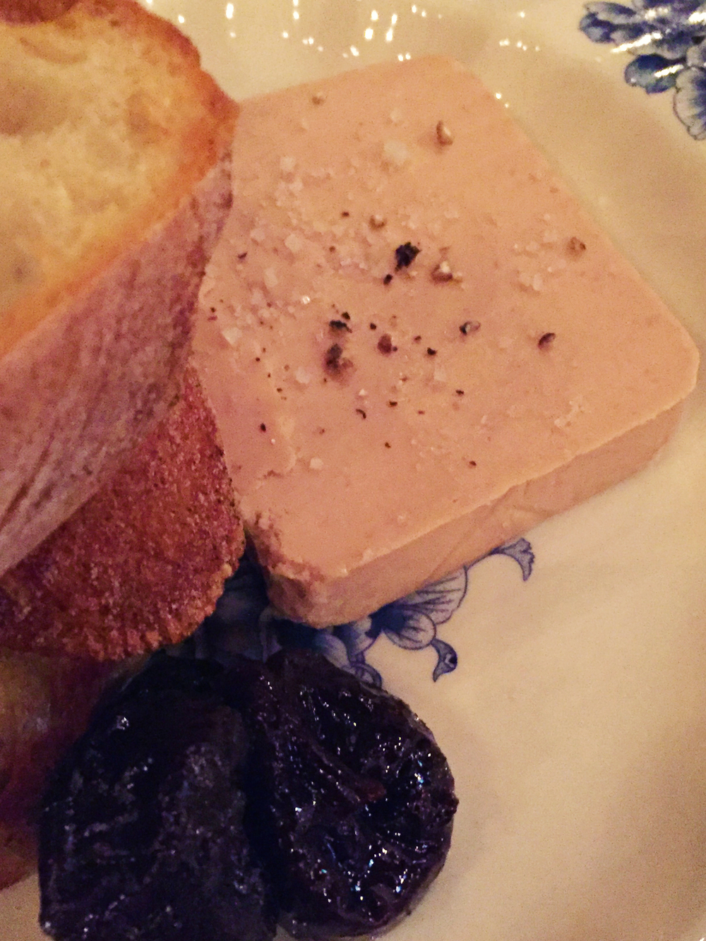 Terrine de Foie Gras with sweet & sour prunes, baguette, and black pepper.