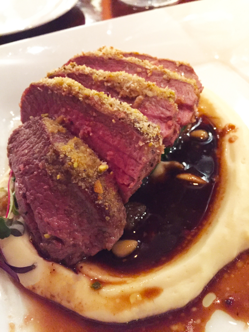 Colorado Lamb Loin with pistachio crust, celery root puree, catalan spinach, and black garlic jus.