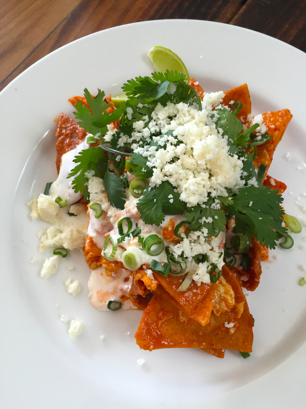 Raymundo's chilaquiles with Mexican sour cream, cilantro, scallion, and cotija.