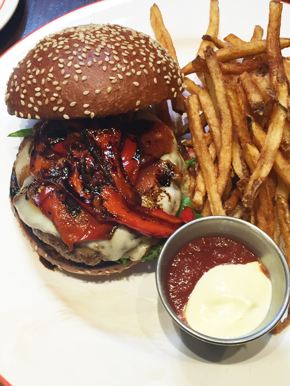 Pepperoni Burger with pork patty, Belcampo by Batali pepperoni, mozzarella, aioli, roasted red bell peppers and balsamic reduction on Bread Bar Brioche & fries.