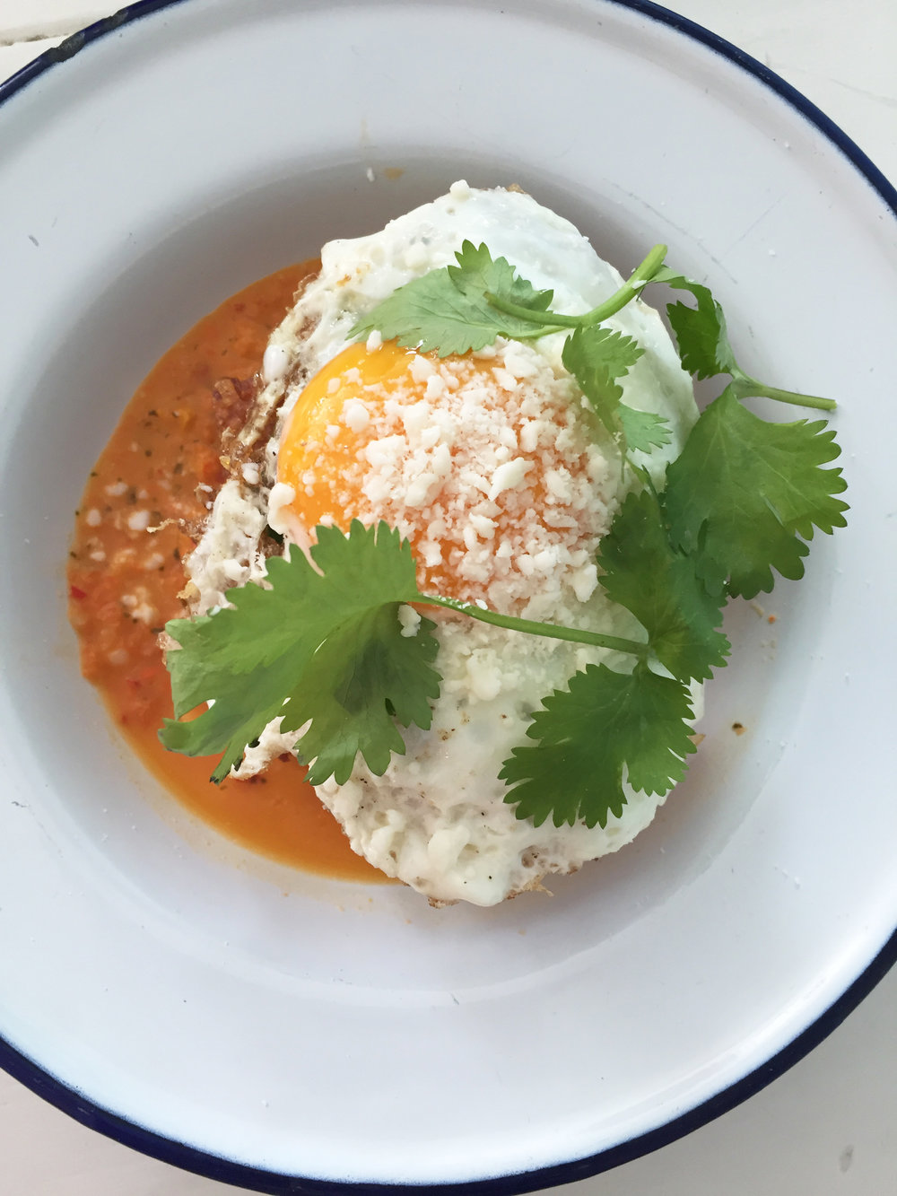 Crispy hash brown chilaquiles with sunny side up egg, cotija, and salsa macho.