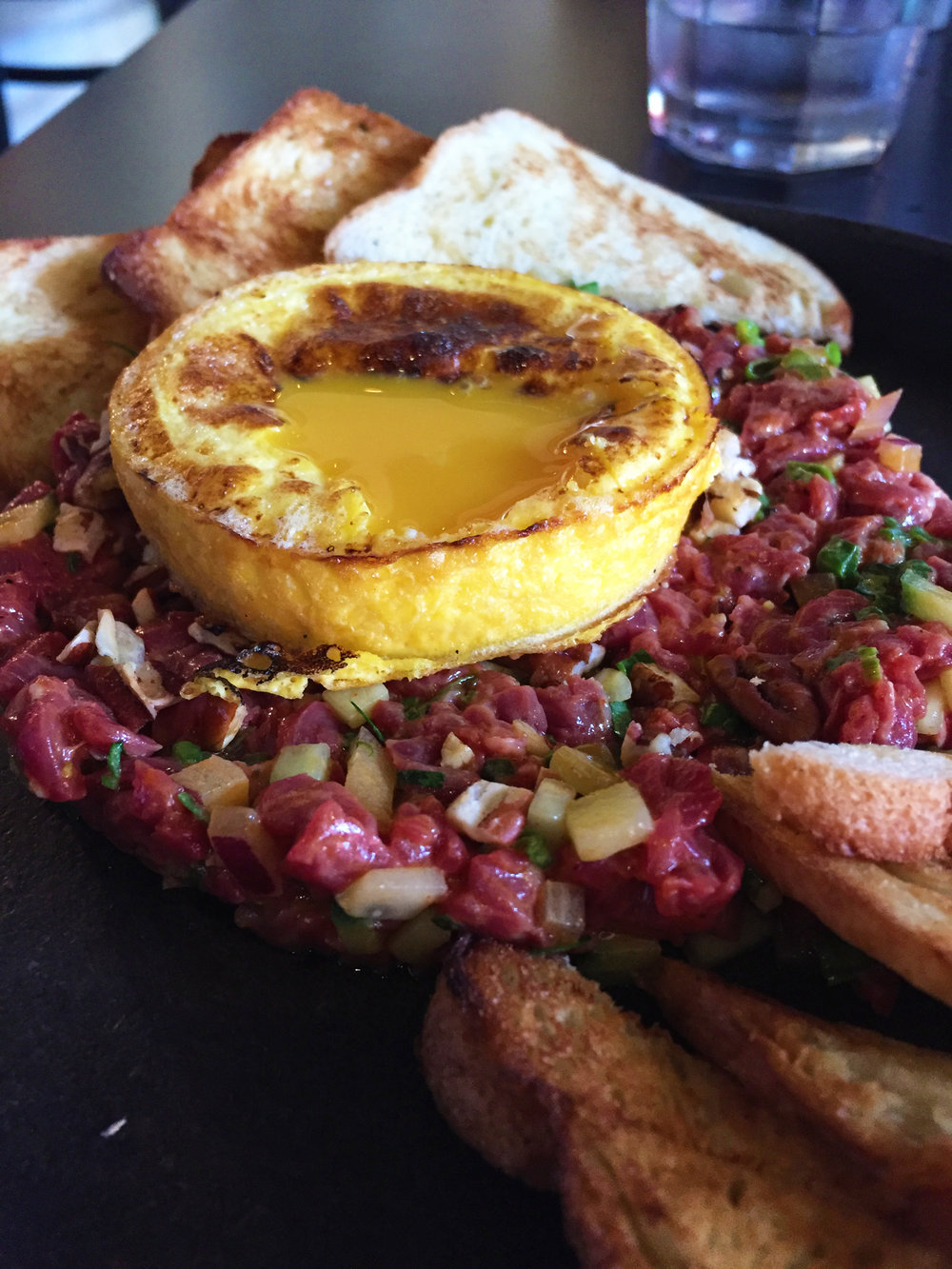 Steak Tartare with chermoula, toast, and seared egg yolk.