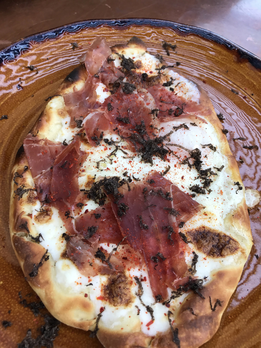 Khachapuri with cheese, egg, prosciutto, truffle, and aleppo