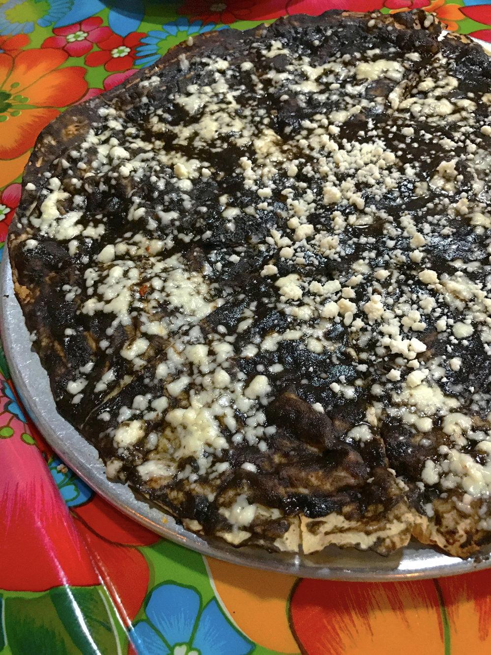 TLAYUDA DE MOLE - tlayuda tortilla topped with black mole