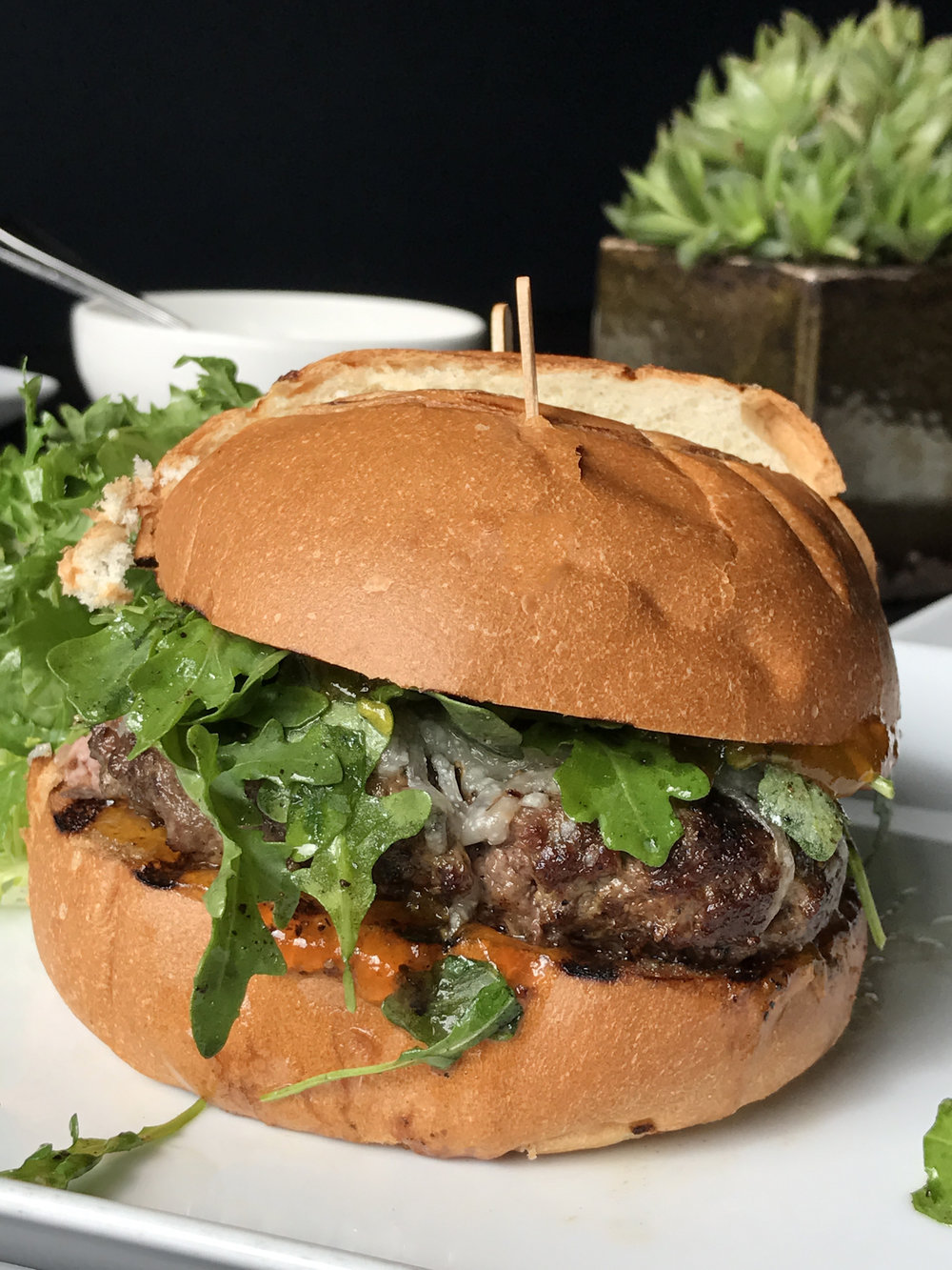 The Tripel Burger with duck confit, pork, and aged beef, arugula, truffle pecorino, house apricot jam, on an onion brioche
