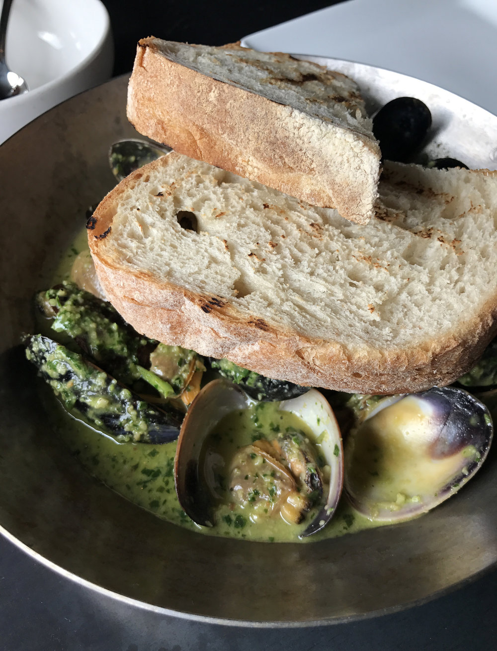 Steamed mussels and clams with serrano pesto broth with cashews and grilled country bread