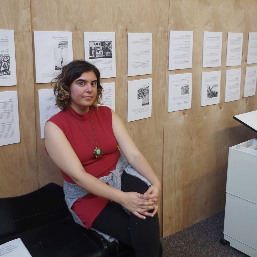 """Feast of Justice"" - a history exhibition I put together as a protest of Feast of Lanterns.  image description: the artist sits on her desk in front of the display, behind her is a timeline."