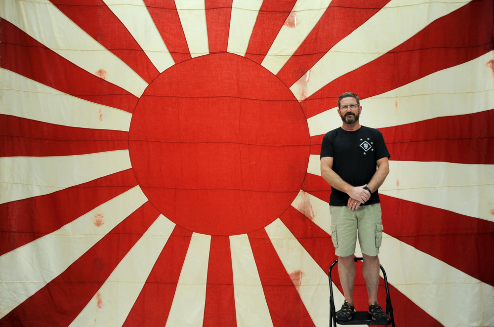 Bill Koehler, president of US Marine Raider Association, and a Japanese flag he is taking back to Japan.