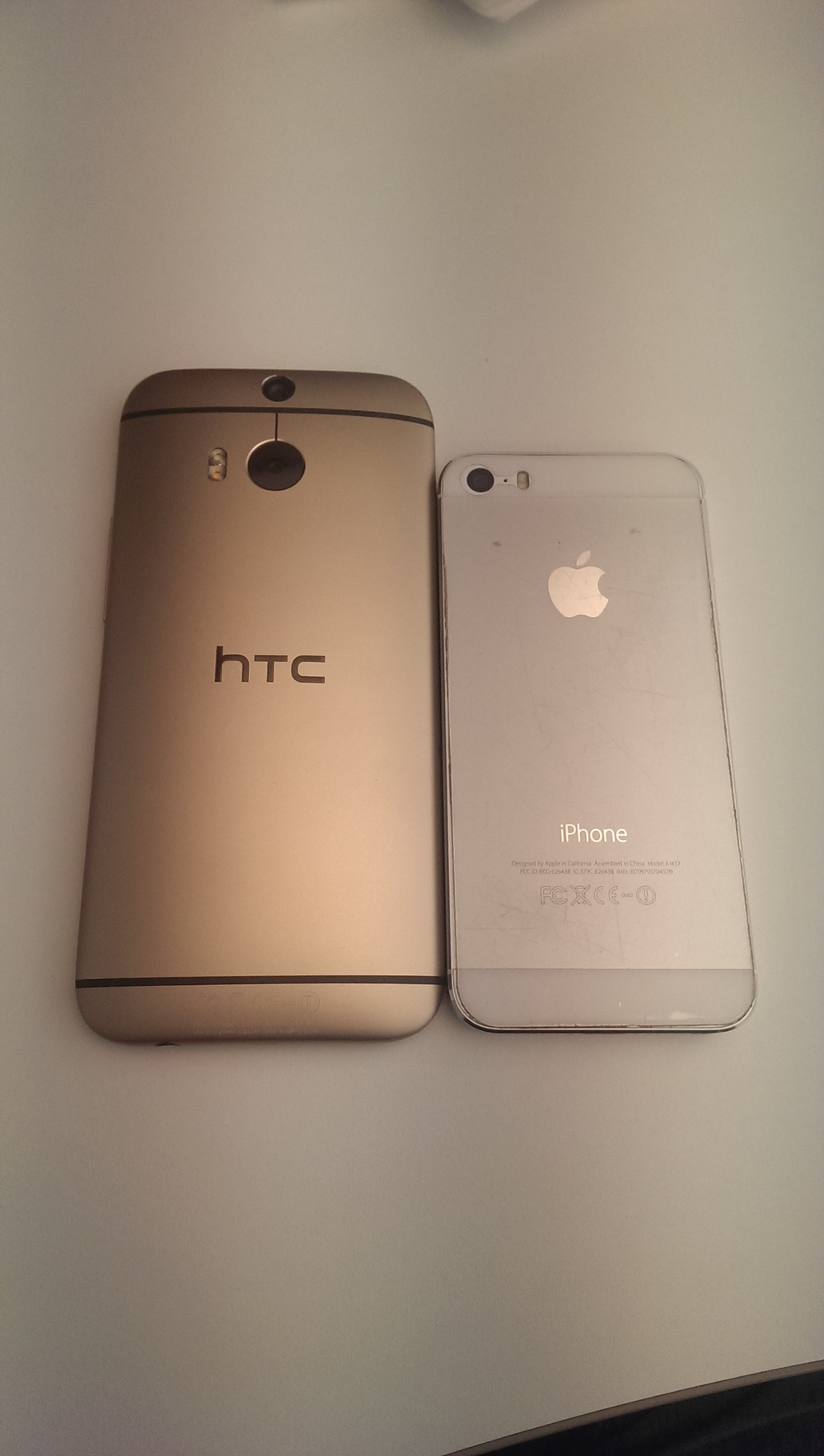 The gold HTC One M8 alongside the silver and white iPhone 5s
