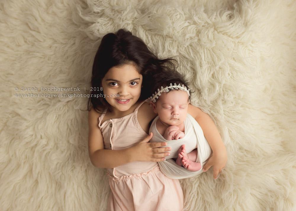 sibling sister newborn posing