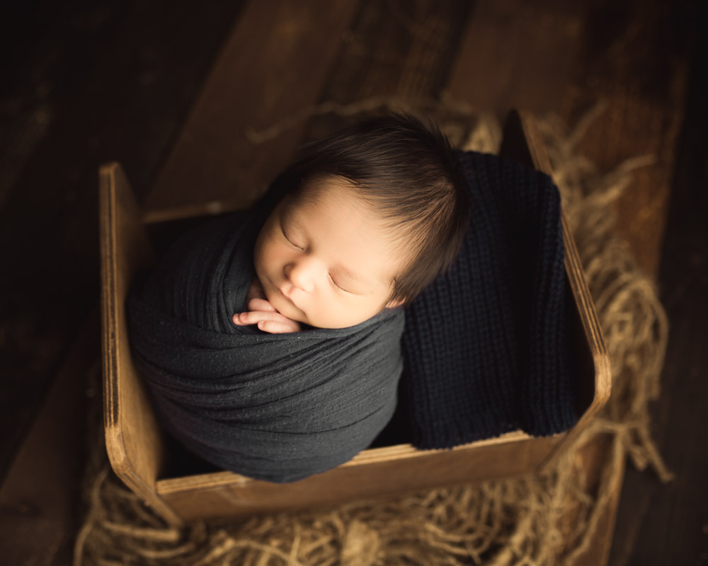 newborn wrapping in miniature bed