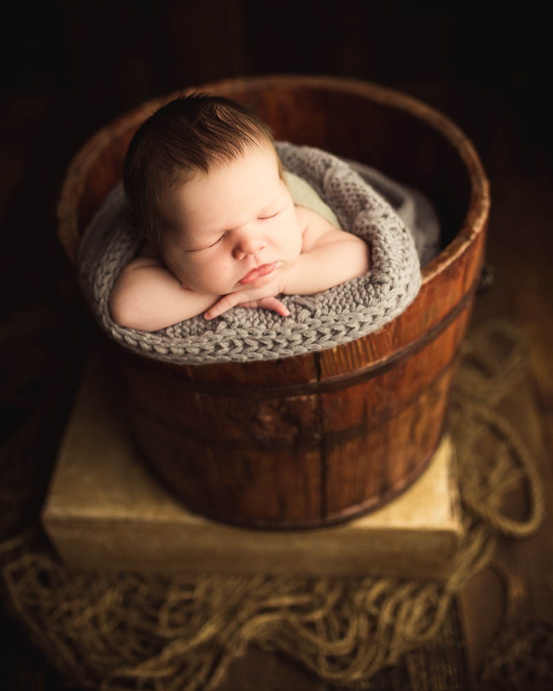 baby in a bucket posed newborn photography