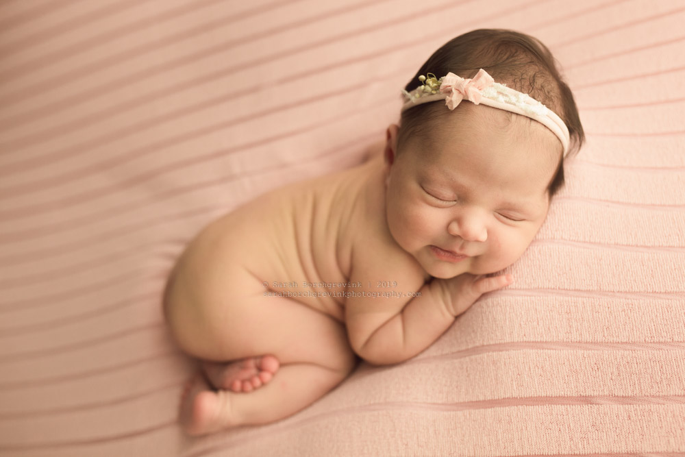 precious baby girl with little smirk smile in newborn session