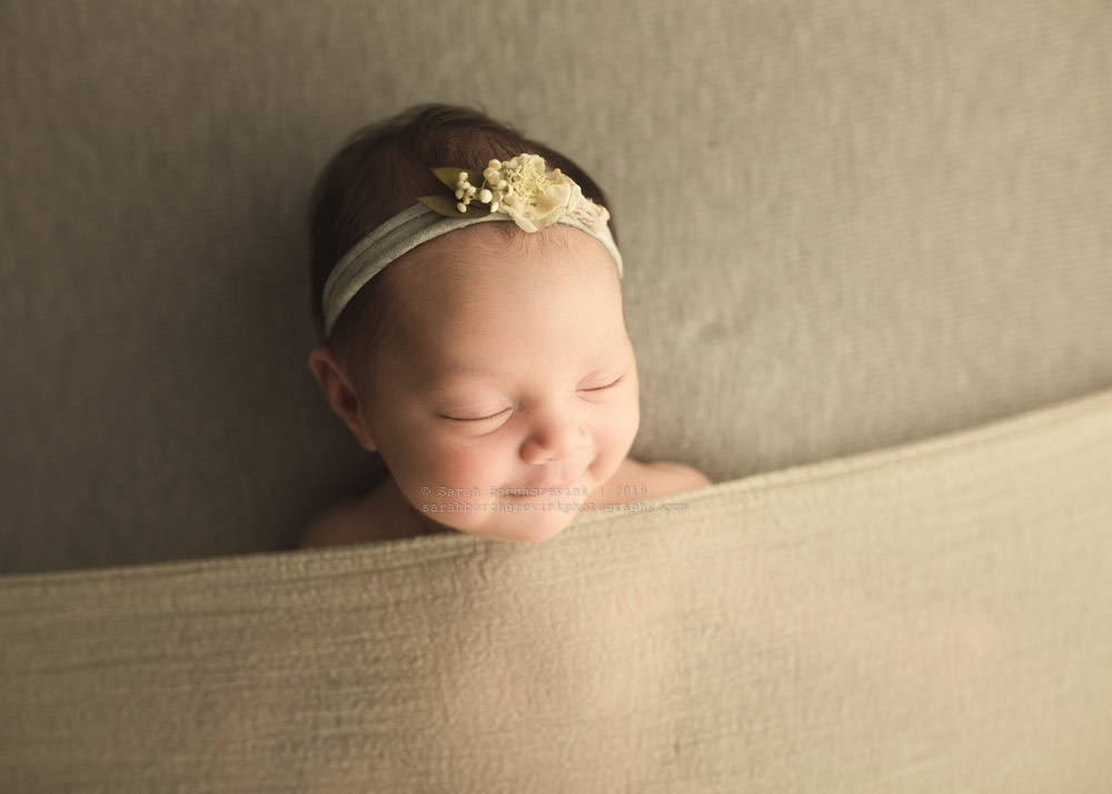 infant girl smiling in her sleep