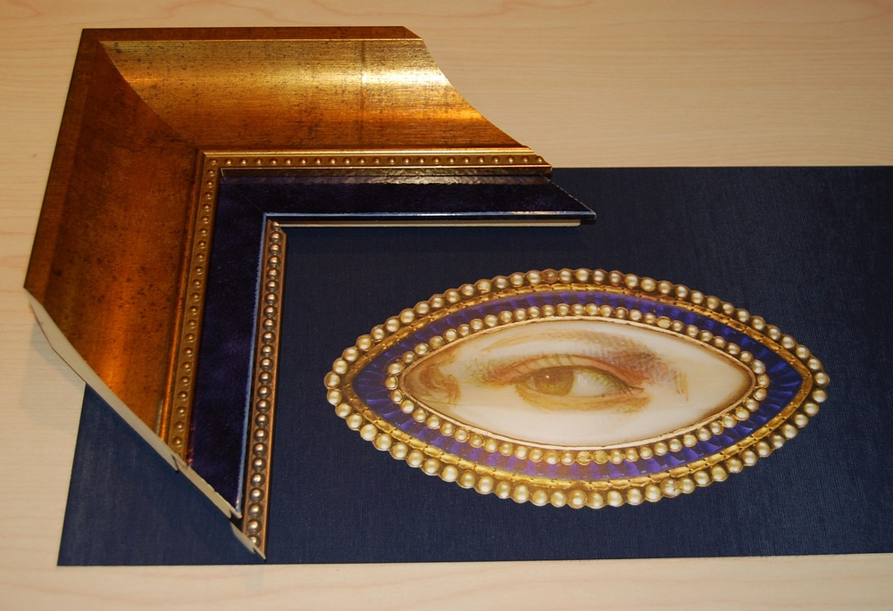 three frames stacked / with cards being mounted on a royal blue linen board
