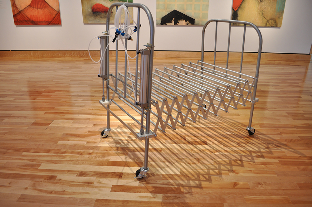 "Procrustean Bed #1. Steel, aluminum, casters and pneumatic actuators. Dimensions variable. 2012. Photo from ""Michael Pittman: Haunted Half"" Exhibition at the Rooms Provincial Art Gallery, St. John's, NL, Canada."