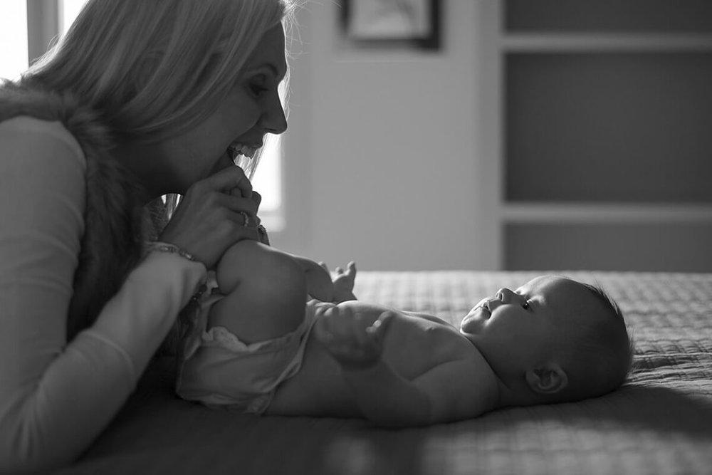 5-Family-Photographer-York_PA-Ken-Bruggeman-Photography-Mom-Playing-Baby-Black-White-Laughing-On-Bed.jpg