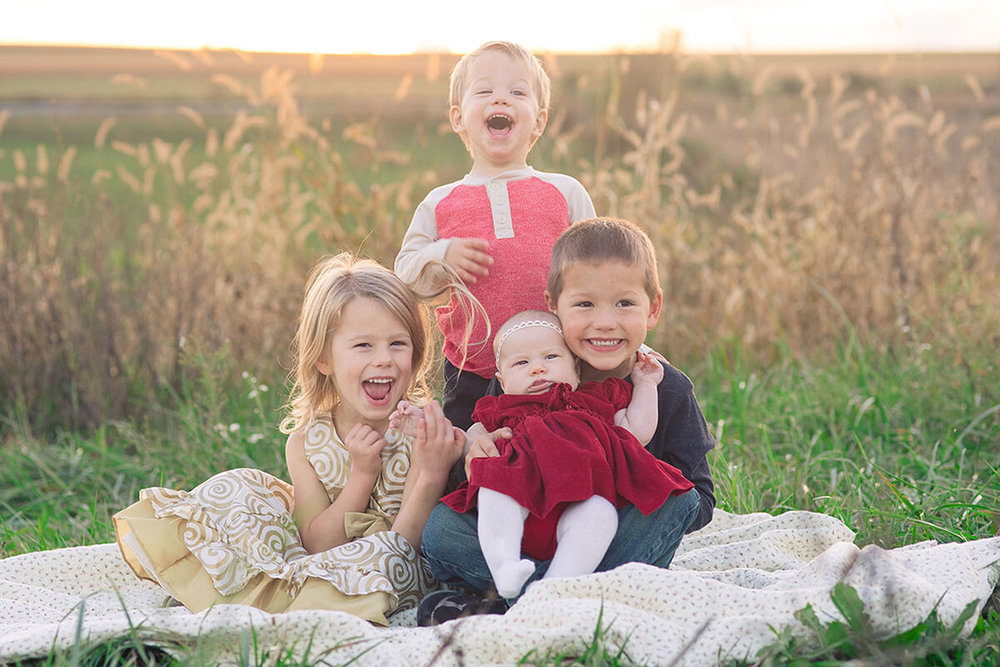 12-Family-Photographer-York-PA-Ken-Bruggeman-Photography-Phillips-Family-Portraits-Four-Children-Sitting-Blanket-Sunset-Laughing.jpg
