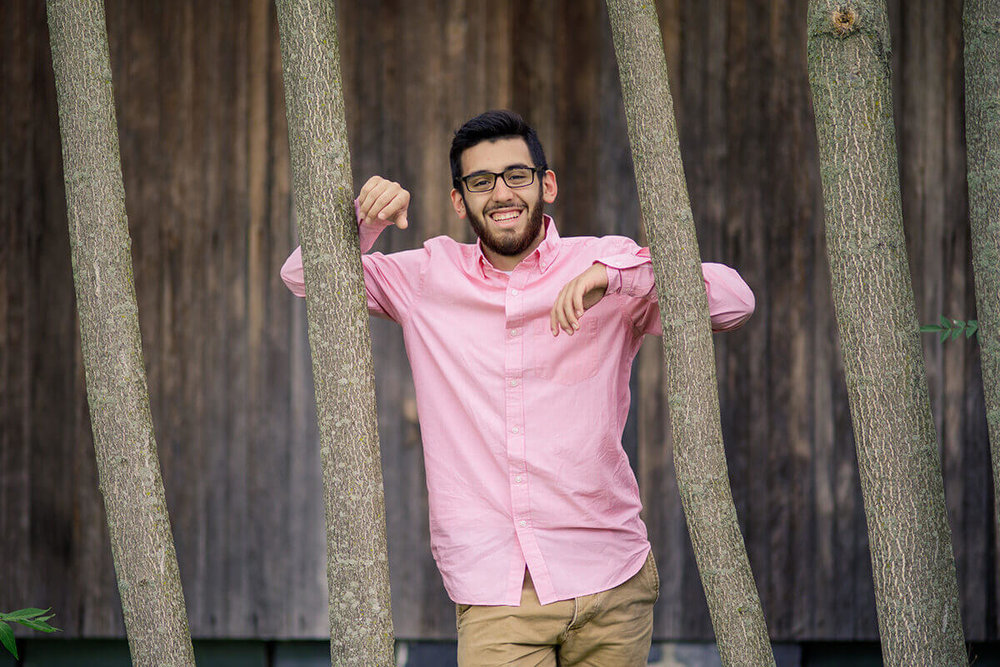 7-Senior-Portrait-Photographer-York-PA-Ken-Bruggeman-Photography-Young-Man-Pink-Shirt-Smiling-Arms-On-Trees.jpg