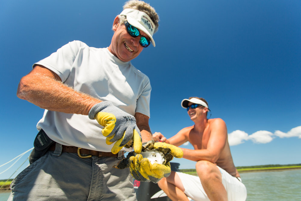 Captain Willie and angler Brian Trow taking a mid-day snack of fresh oysters
