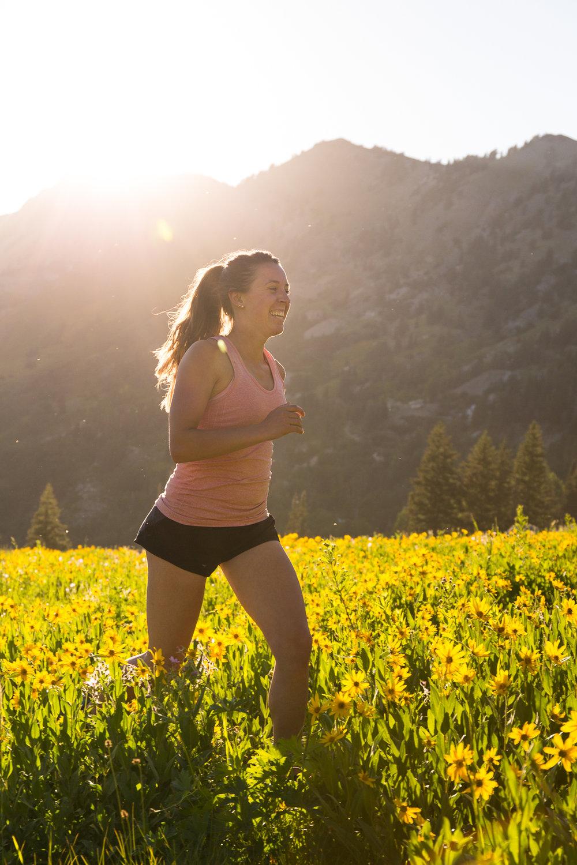 Kaytlin Hughes trail running in the summer wildflowers near Alta Ski Resort in Utah