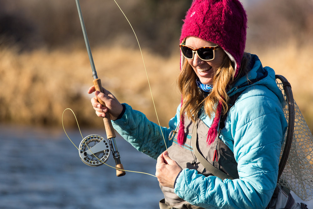 Heidi Lewis fly fishing on the Middle Provo River with her dog outside of Midway, Utah