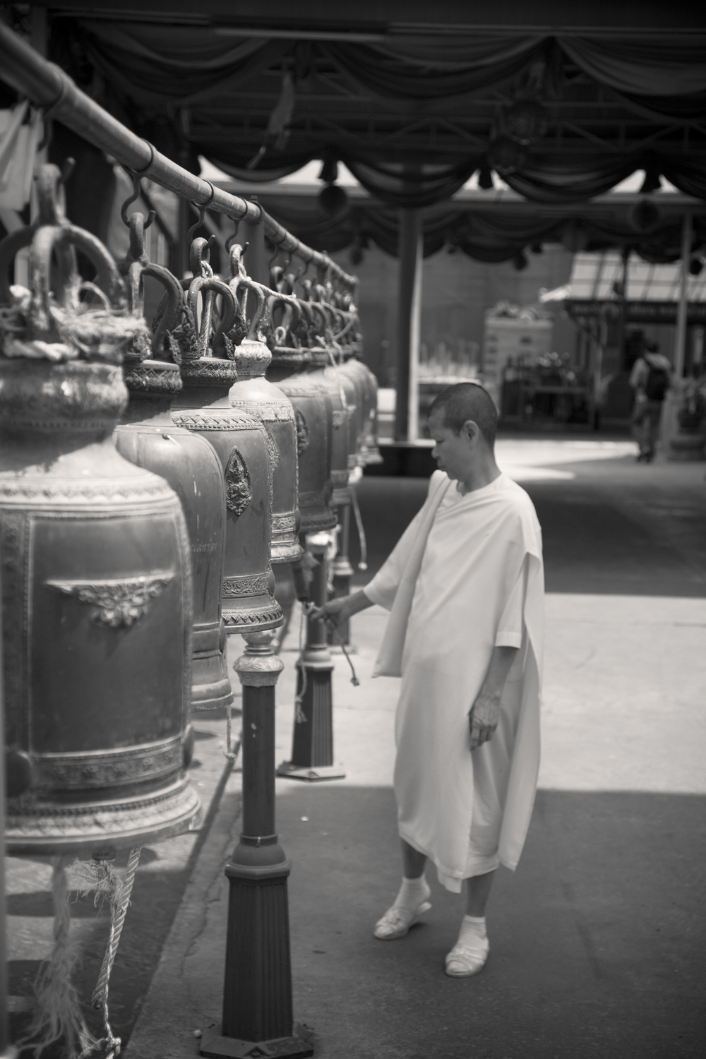 A Buddhist Nun rings the bells in the grounds of Wat Kalayanamitr