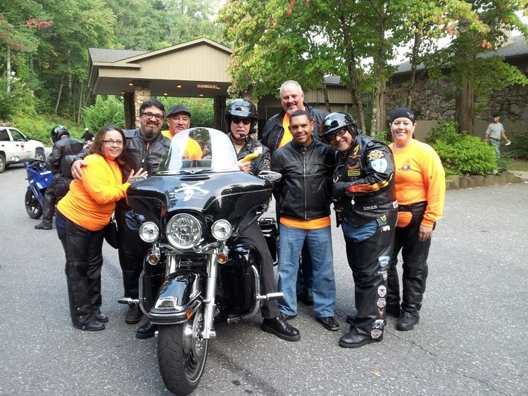 Pastor Tom Hughes sits on his Harley and AMM National President Juan Santos  stands to the right wearing a helmet.