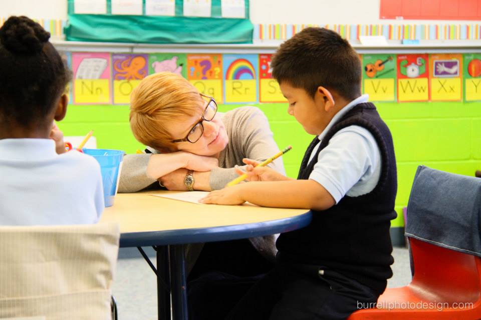 Mrs. Bartley takes time to help one of her Kindergarten scholars think through his assignment.