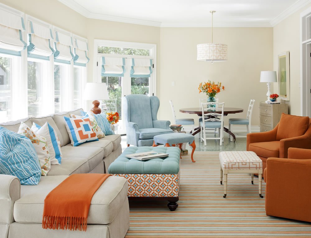 Unlike the previous spaces, this family room by Tobi Fairley uses nearly equal doses of its complementary colors, sky blue and coral.  This works because the colors are of matching strength and vividness, and the background is a creamy beige.