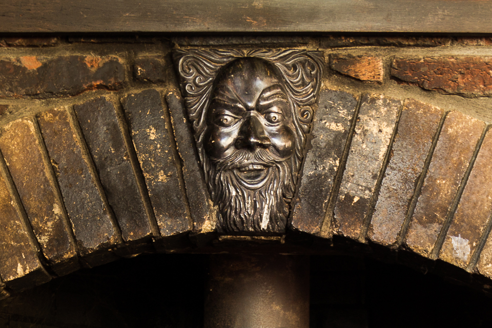 Earth House bronze fireplace detail. Gee, that face looks familiar.