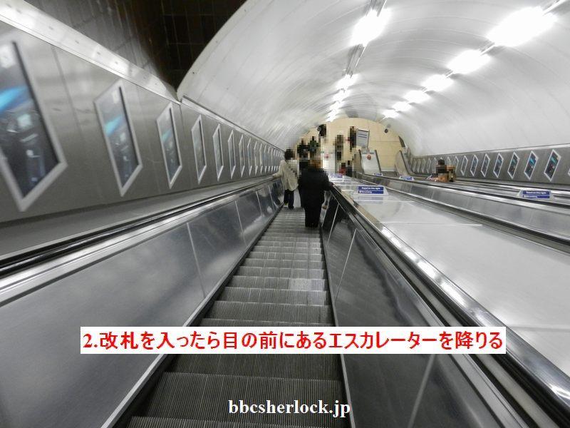 改札を通ったら、地下ホームへ続く長いエスカレーターがあります。下りエスカレーターに乗って下まで降りましょう。