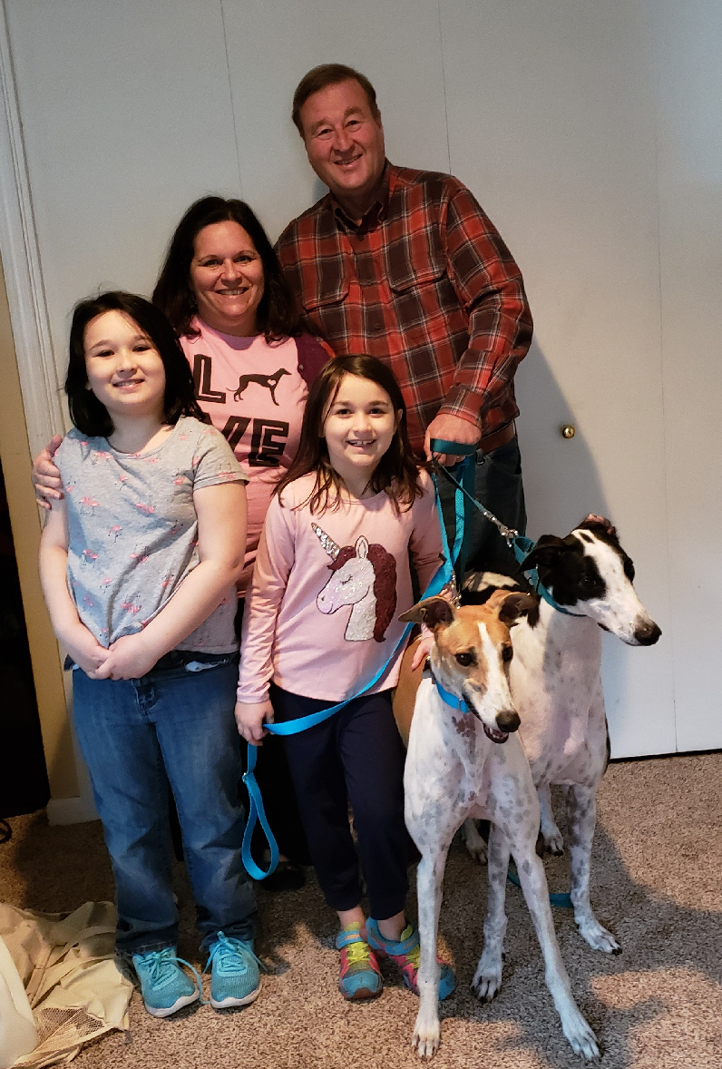 "Another Hardee Graduate and a Plus 1 !! Congratulations to Jane, Paul, Kate and Claire with their new ""siblings"", Sunny (white and fawn) and BRGA's recently sponsored broken leg dog, Lenny! The family waited patiently for several months to take the trip to FL to pick up Nevaeh, now called Sunny from the Hardee Hero Hound program on December 7. Sunny is a sweet, shy little female that was loved by her trainer at Hardee! Jane, Paul and their daughters immediately fell in love with her too!  After graduation, the family agreed to take on an extra passenger, Lenny, to be adopted in VA. Well, not halfway through Lenny's ride to VA, the Anderson's knew he was a part of their family! It turns out that Sunny and Lenny are related! Lenny and Sunny have been inseparable ever since! Lenny officially retired with his new family on December 9!  Please welcome everyone to the BRGA pack!"