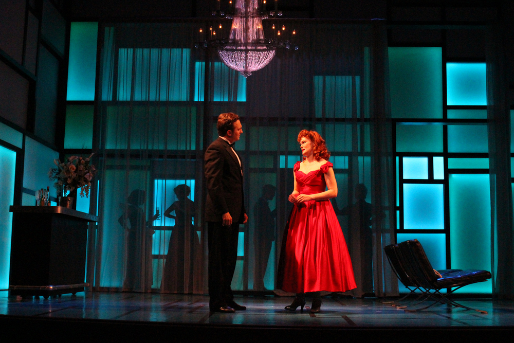 ELLA SAYS GOODBYE TO JEFF IN LARRY'S PENTHOUSE. THE SPACE UPSTAGE OF THE WINDOW/SHEER CURTAINS WAS PLAYED AS A BALCONY